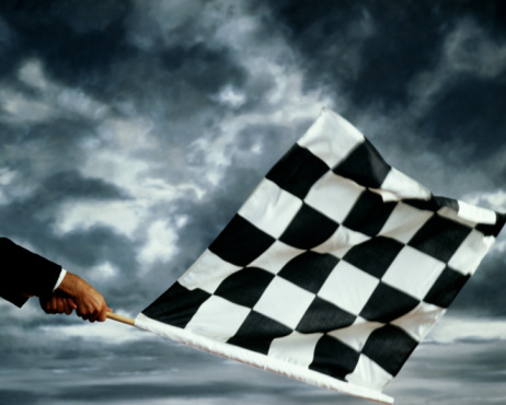 Hands waving black and white chequered flag, cloudy sky in back ground